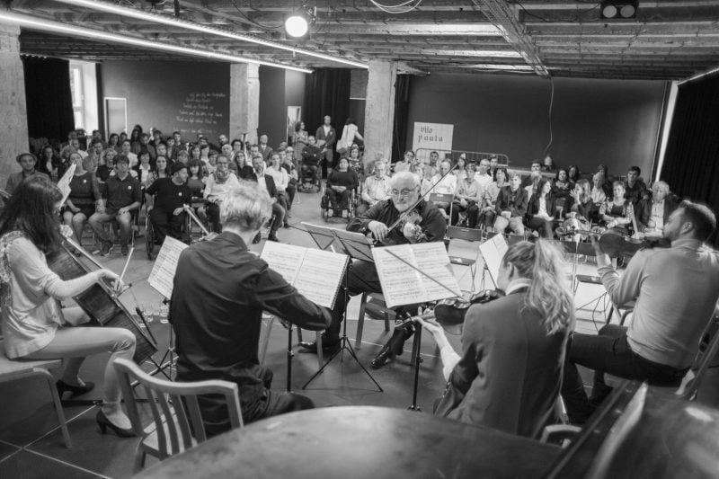 Čiernobiela fotka orchestru na vystúpení | Hendikup