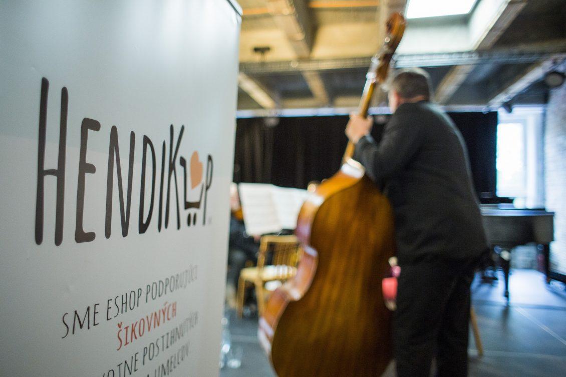 Fotka logo hendikup v pozadi hrá člen orchestru na basu | Hendikup